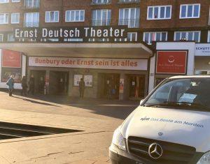 Haupteingang des Ernst Deuitsch Theaters, ein Wagen des NDR im Vordergrund. Gäste gehen zum Eingang