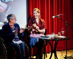 auf dem Foto sieht man Kerstin Hagemann von der Patienten-Initiative und Birte Müller. Beide sitzen vor einem roten Theatervorhang. Man sieht einen Tisch mit Büchern und einen Ständer mit einem Mikrophon. Birte Müller hält den Preis in der Hand und strahlt. Kerstin Hagemann lacht auch und applaudiert.