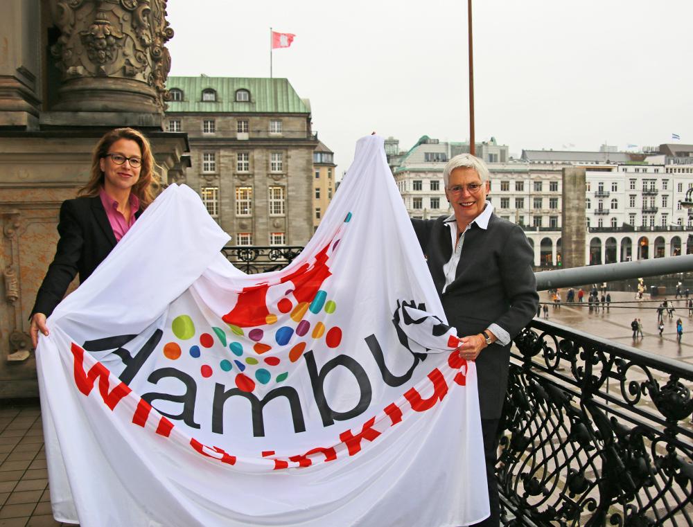 Carola Veit und Ingrid Körner halten die Fahne in den Händen