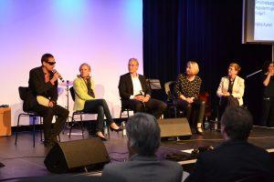 Die Bühne im Resonanzraum mit der Moderatorin und den vier Gesprächspartnerinnen. Sie sitzen in einer Reihe, die Bühne ist von hinten hell beleuchtet. Heiko Kunert sitzt ganz links und spricht gerade in ein Handmikrofon. Die anderen haben ihre Köpfe zu ihm gewandt. Im Vordergrund sieht man einige Zuschauer der ersten Reihe.